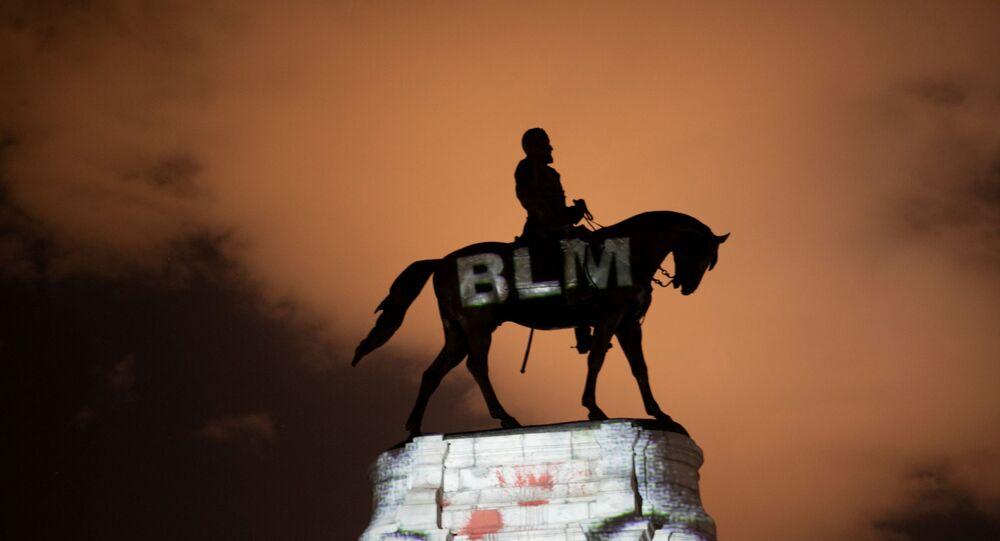 Artist Dustin Klein projects a Black Lives Matter image onto the statue of Confederate General Robert E. Lee in Richmond, Virginia, U.S. June 18, 2020.