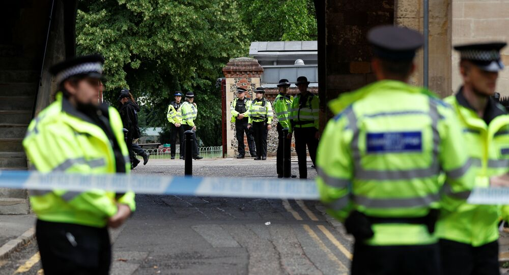 Police officers stand behind the cordon at the scene of multiple stabbings in Reading, Britain, June 21, 2020.