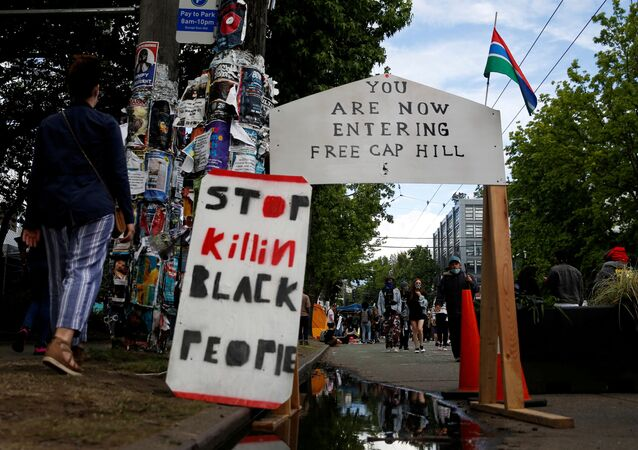 People walk by signs at a barrier set up at the edge of the self-proclaimed CHAZ/CHOP zone around the Seattle Police Department's East Precinct as people call for the defunding of police and protest against racial inequality in the aftermath of the death in Minneapolis police custody of George Floyd, in Seattle, Washington, U.S. June 14, 2020