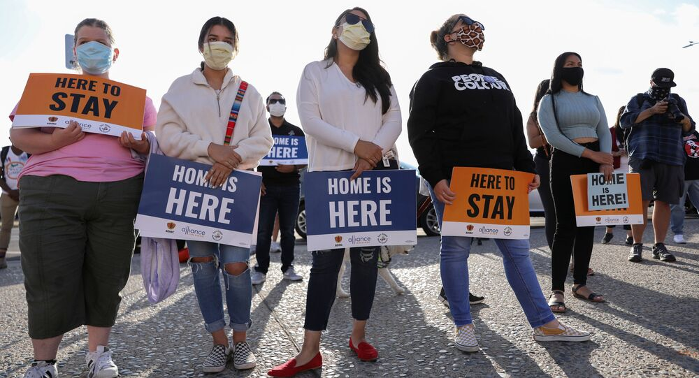 People hold signs as they take part in a rally for Justice Everywhere to celebrate the U.S. Supreme Court's ruling to disallow the rescinding of the Deferred Action for Childhood Arrivals (DACA) program, in San Diego, California, U.S., June 18, 2020.