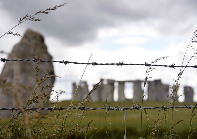 The Stonehenge stone circle is seen through a barbed wire, where official Summer Solstice celebrations were cancelled due to the spread of the coronavirus disease (COVID-19), near Amesbury, Britain June 20, 2020