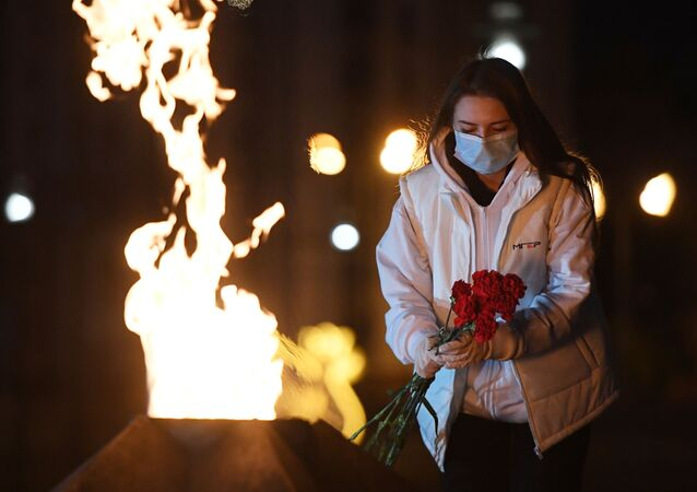 A woman during the international 'Candle of Memory' vigil, dedicated to the 75th anniversary of the start of World War II at the Eternal Flame in Kazan, Russia's Victory Park.