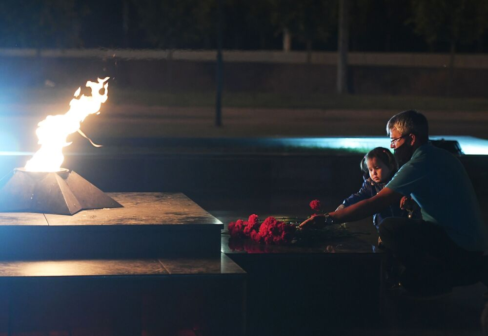 A man with a child during the international Candle of Memory event, dedicated to the 75th anniversary of the start of World War II, at the Eternal Flame in Victory Park in Kazan.