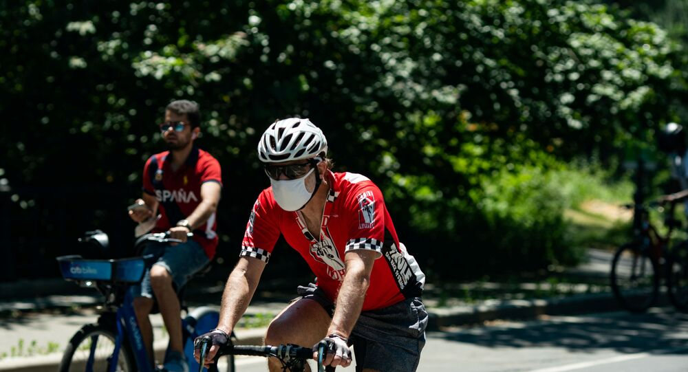 A man wearing a protective mask rides a bicycle in Central Park, the day before the city starts phase two of reopening after the lockdown due to the coronavirus disease (COVID-19), in the Manhattan borough of New York City, U.S., June 21, 2020.