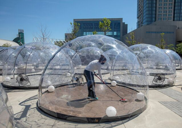 An employee cleans the dome before an outdoor yoga class by LMNTS Outdoor Studio, in a dome to facilitate social distancing and proper protocols to prevent the spread of coronavirus disease (COVID-19), in Toronto, Ontario, Canada June 21, 2020.