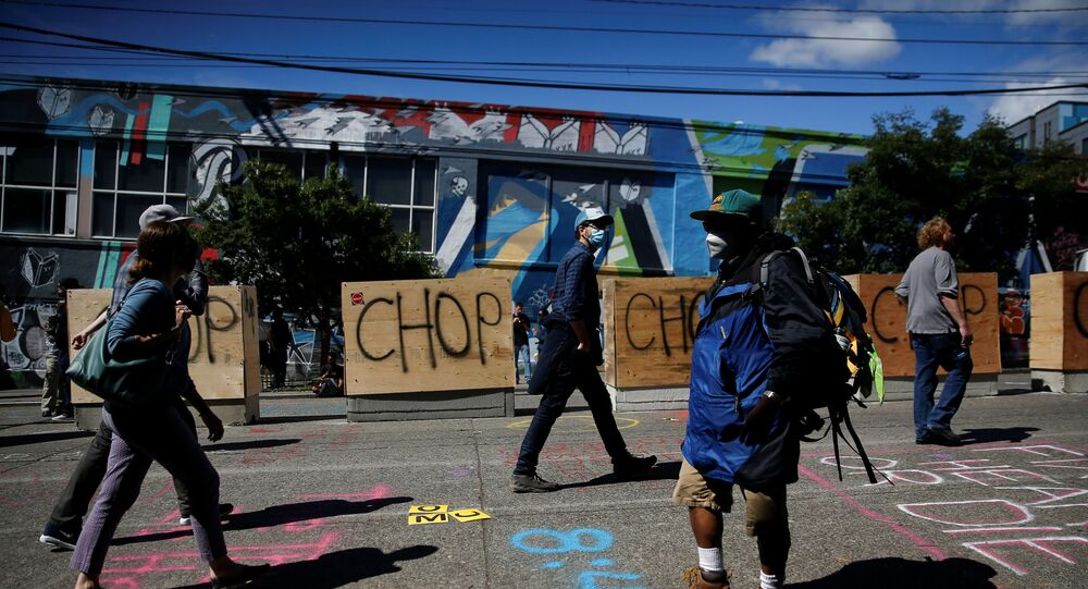 People walk by concrete barriers newly installed by the city as protesters demonstrate against racial inequality and occupy space at the CHOP area near the Seattle Police Department's East Precinct in Seattle, Washington, U.S. June 16, 2020.
