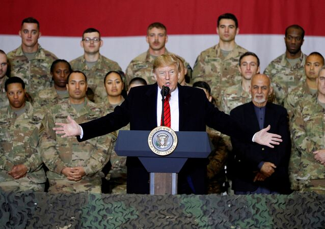 US President Donald Trump delivers remarks to US troops, with Afghanistan's President Ashraf Ghani standing behind him, during an unannounced visit to Bagram Air Base, Afghanistan,  28 November 2019