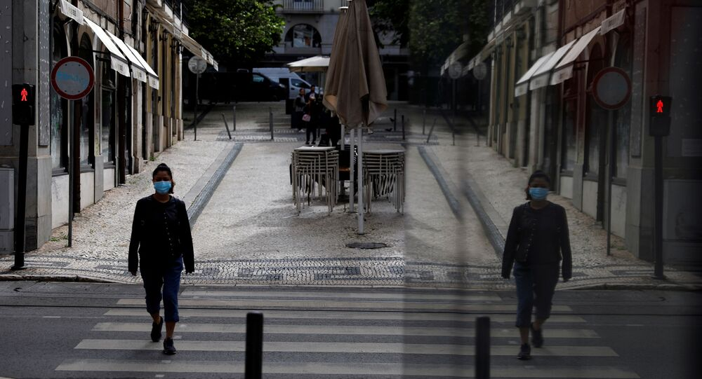 A woman wearing a protective mask walks, amid the coronavirus disease (COVID-19) outbreak, in downtown Lisbon, Portugal, May 14, 2020