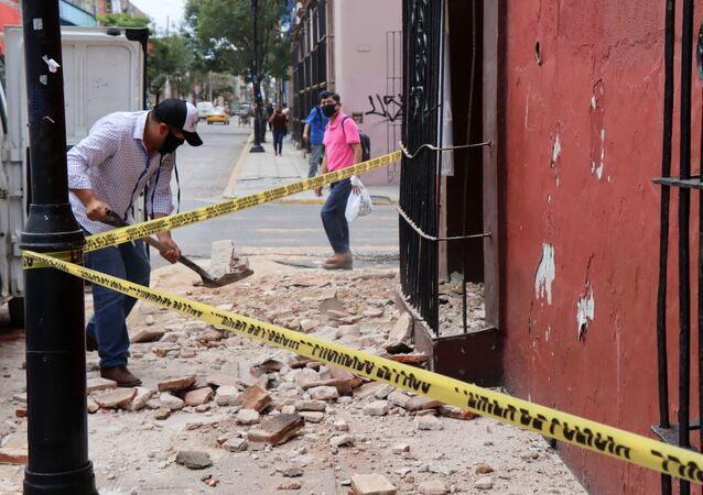 A man removes debris from a building damaged during a quake, in Oaxaca, Mexico