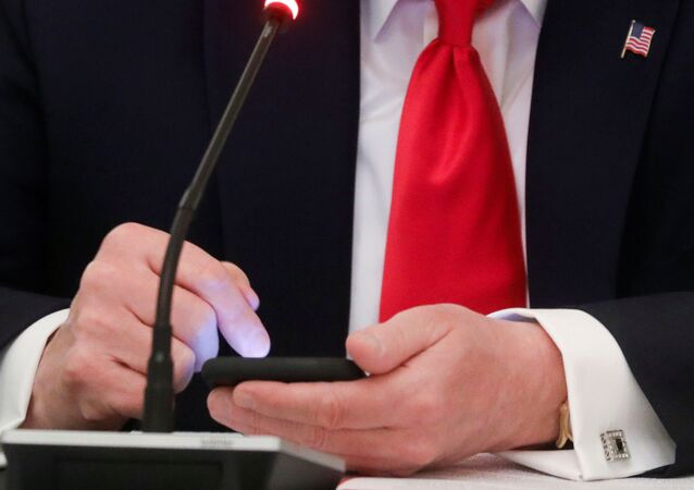 U.S. President Donald Trump is seen tapping the screen on a mobile phone at the approximate time a tweet was released from his Twitter account, during a roundtable discussion on the reopening of small businesses in the State Dining Room at the White House in Washington, U.S., June 18, 2020
