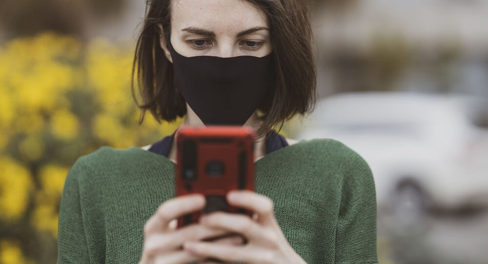 A woman wearing a face mask holds up her mobile phone