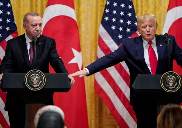 U.S. President Donald Trump reaches to Turkey's President Tayyip Erdogan during a joint news conference at the White House in Washington, U.S., November 13, 2019