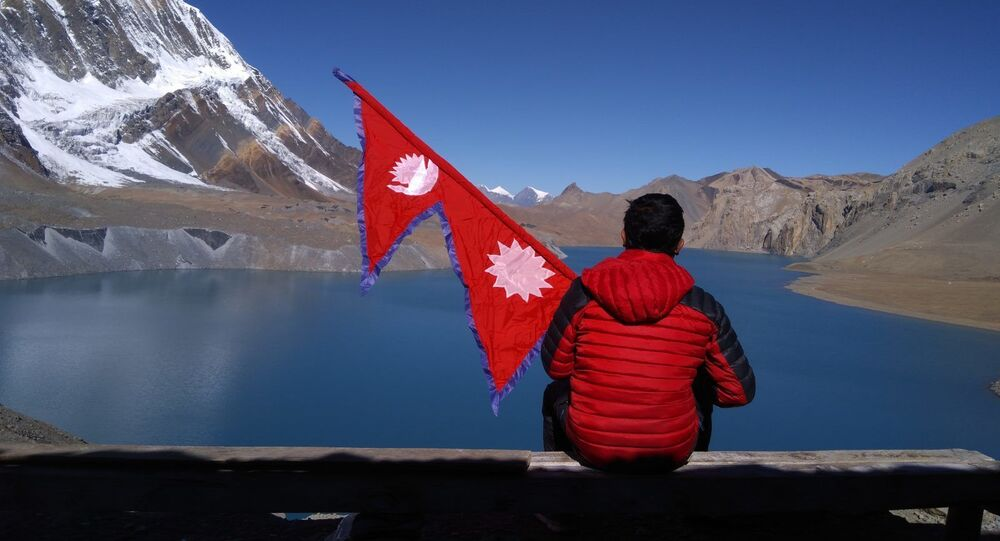 Man sitting on the shore of Tilicho Lake in Nepal, holding flag