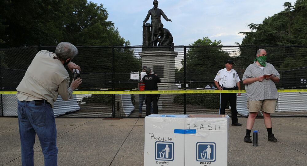 A park attendee takes a cell phone photo while another reads a book outside of an enclosed statue of U.S. President Abraham Lincoln, ahead of a demonstration calling for the removal of the statue at Lincoln Park near the U.S. Capitol in Washington, U.S. June 25, 2020