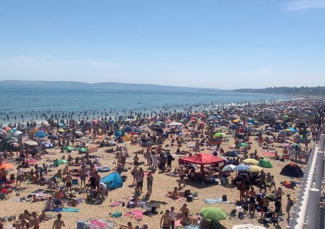 People enjoy the hot weather at the beach, amid the outbreak of the coronavirus disease (COVID-19), in Bournemouth, Britain, 25 June 2020 in this still image obtained from a social media video.