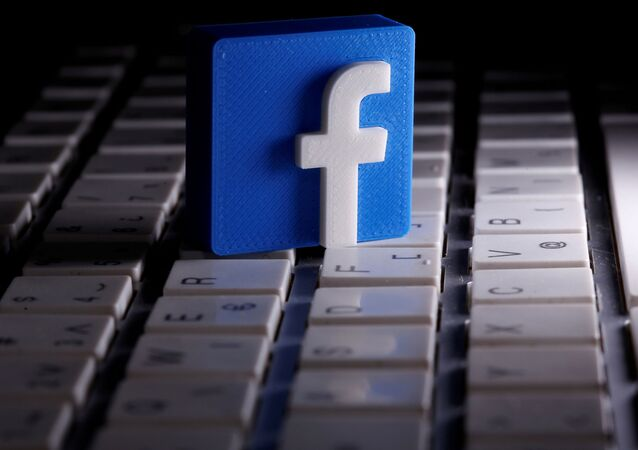 A 3D-printed Facebook logo is seen placed on a keyboard in this illustration taken March 25, 2020
