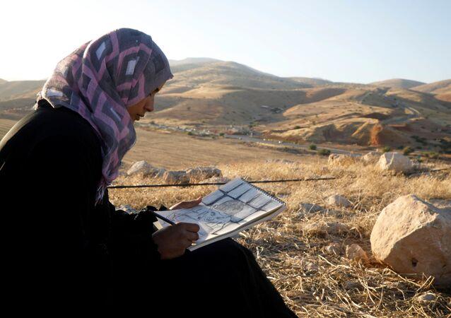 Khadeeja Bisharat, a Palestinian artist, draws in Jordan Valley in the Israeli-occupied West Bank June 18, 2020. Picture taken June 18, 2020