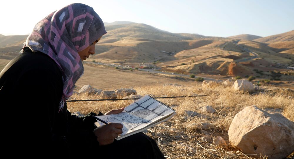 Khadeeja Bisharat, a Palestinian artist, draws in Jordan Valley in the Israeli-occupied West Bank June 18, 2020. Picture taken June 18, 2020