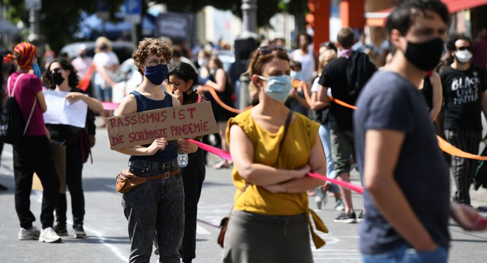 A person holds a banner reading Racism is the worst pandemic as participants of the so-called Indivisible demonstration form a human chain in support of the Black Lives Matter movement and to protest against the lockdown following the coronavirus disease (COVID-19) outbreak, in Berlin, Germany, June 14, 2020.
