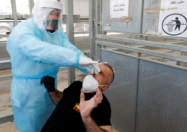 A healthcare worker swabs the nose of a Palestinian worker for the coronavirus disease (COVID-19) testing upon his return from Israel, outside the Israeli-controlled Meitar checkpoint, near Hebron in the Israeli-occupied West Bank April 7, 2020.