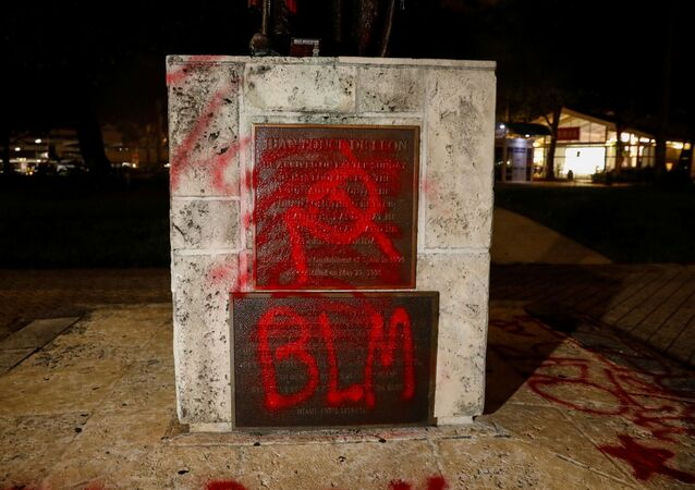 Graffiti is seen on a vandalized statue of Christopher Columbus at the Bayside Marketplace, after a protest against racial inequality in the aftermath of the death in Minneapolis police custody of George Floyd, in Downtown Miami, Florida, U.S., June 10, 2020.