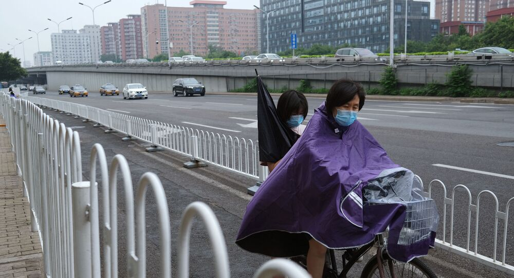 A woman wearing a raincoat and face mask amid rainfall in Beijing
