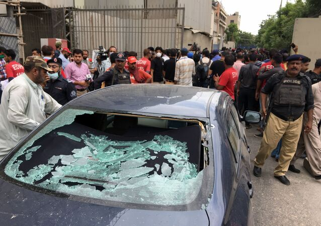 A plainclothes police officer (L) surveys the site of an attack at the Pakistan Stocks Exchange entrance in Karachi June 29, 2020