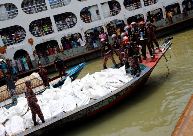 Rescue members stand near the bodies on a boat after a passenger ferry capsized in the river Buriganga in Dhaka, Bangladesh, June 29, 2020