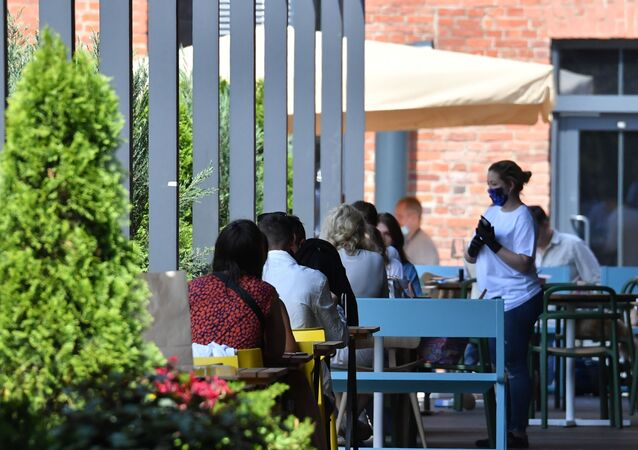 Server takes an order from customers after the opening of outdoor cafes in Moscow in mid-June.