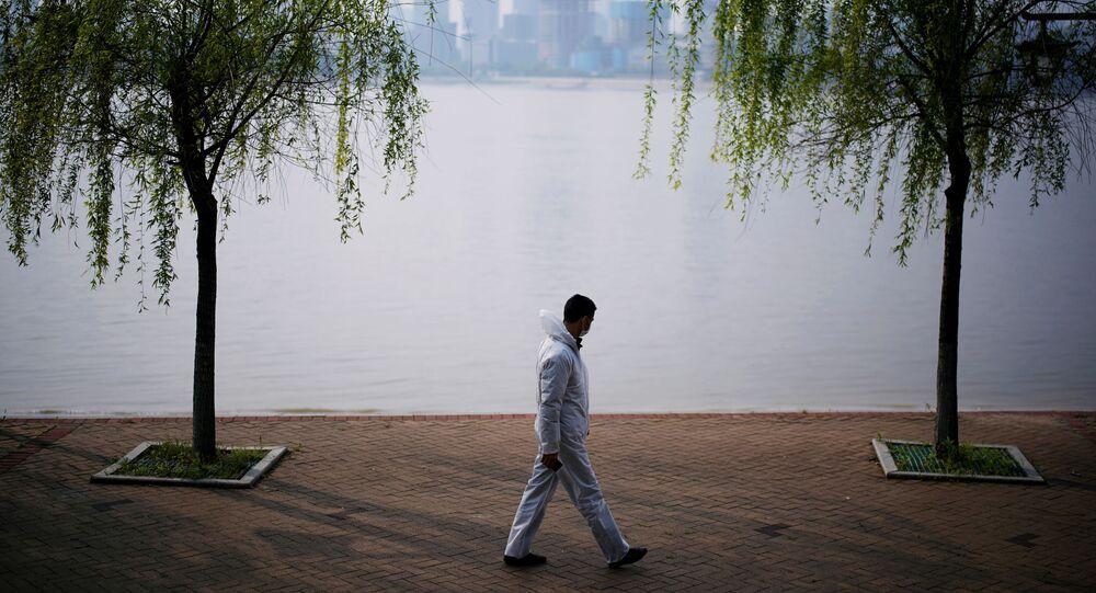 A man wearing protective gear walks by the Yangtze river in Wuhan, Hubei province, on April 4, 2020.
