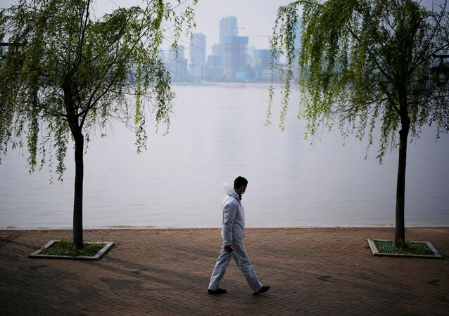 A man wearing protective gear walks by the Yangtze river in Wuhan, Hubei province, on April 4, 2020.