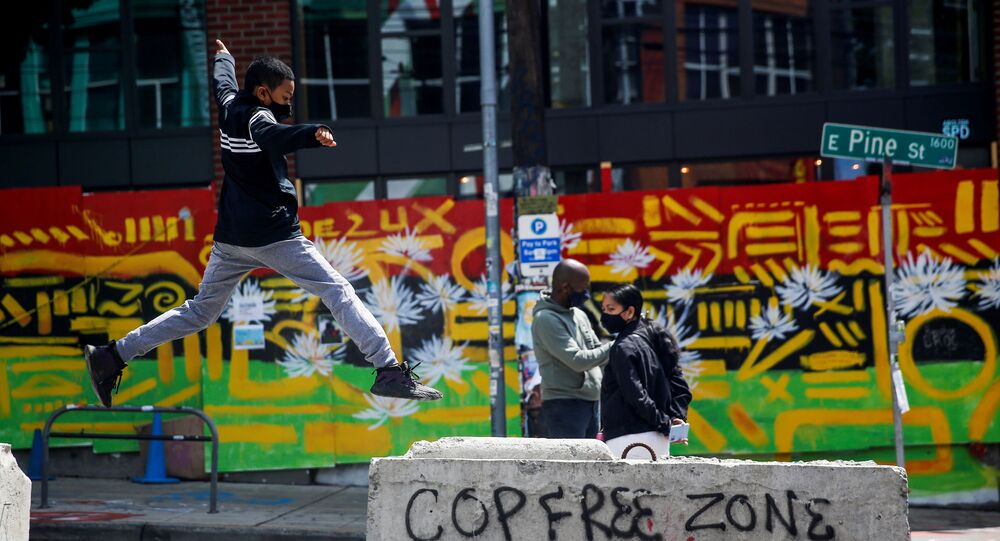 Jamil jumps onto a barricade with graffiti reading Cop free zone as his parents stand nearby at the CHOP area as people continue to occupy space and protest against racial inequality in the aftermath of the death in Minneapolis police custody of George Floyd, in Seattle, Washington, U.S. June 28, 2020.