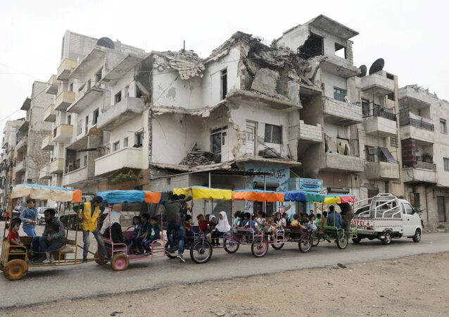 Children ride in carts past a damaged building on the first day of the Muslim holiday of Eid al-Fitr, amid the global outbreak of the coronavirus disease (COVID-19), in the opposition-held Idlib city in northwest Syria, May 24, 2020.