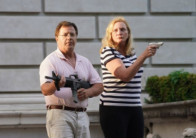 Mark and Patricia McCloskey draw their firearms on protestors as they enter their neighborhood during a protest against St. Louis Mayor Lyda Krewson, in St. Louis, Missouri, U.S. June 28, 2020.