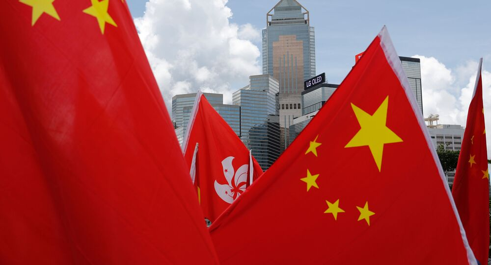 Buildings are seen above Hong Kong and Chinese flags, as pro-China supporters celebration after China's parliament passes national security law for Hong Kong, in Hong Kong, China June 30, 2020