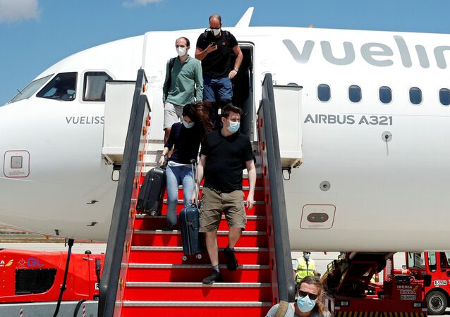 Passengers leave a Vueling plane upon their arrival at Palma de Mallorca airport on the Balearic Islands, Spain, June 13, 2020.