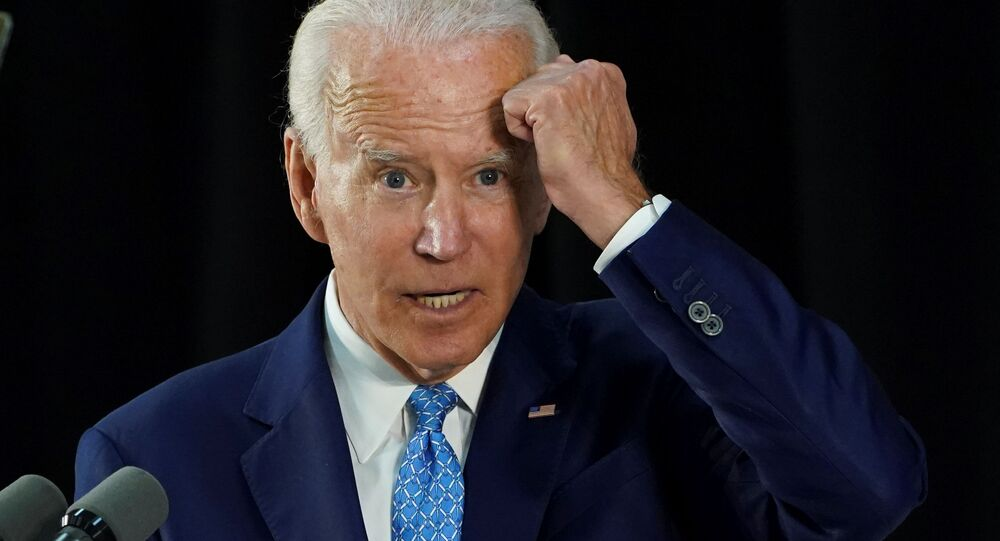 Democratic U.S. presidential candidate and former Vice President Joe Biden gestures with his fist towards his head as he says he has not been tested for coronavirus because he has had no symptoms as my mother would say, knock on wood while answering questions from reporters during a campaign event in Wilmington, Delaware, U.S., June 30, 2020.