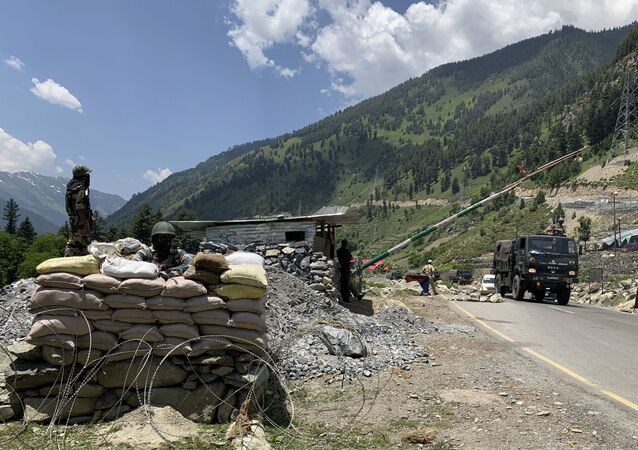 Indian paramilitary soldiers keep guard as Indian army convoy moves on the Srinagar-Ladakh highway at Gagangeer, north-east of Srinagar, India, Thursday, June 18, 2020.