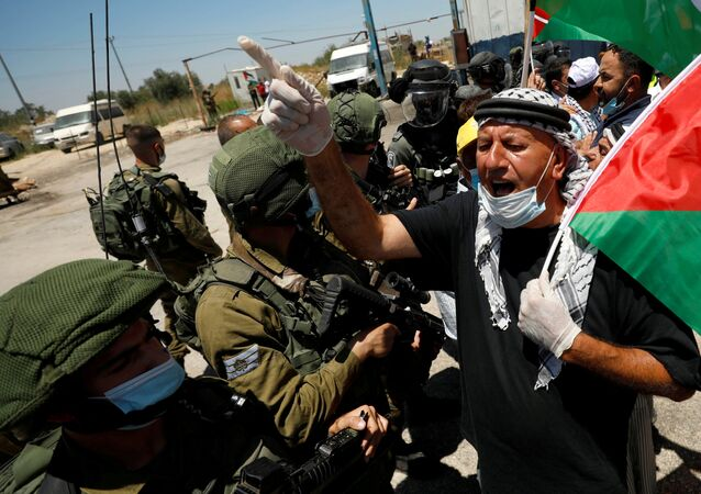 FILE PHOTO: A demonstrator holding a Palestinian flag gestures in front of Israeli forces during a protest against Israel's plan to annex parts of the occupied West Bank, in Haris June 26, 2020.