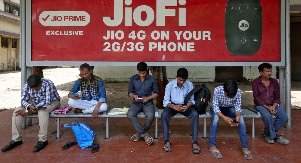 Commuters use their mobile phones as they wait at a bus stop with an advertisement for Reliance Industries' Jio telecoms unit, in Mumbai