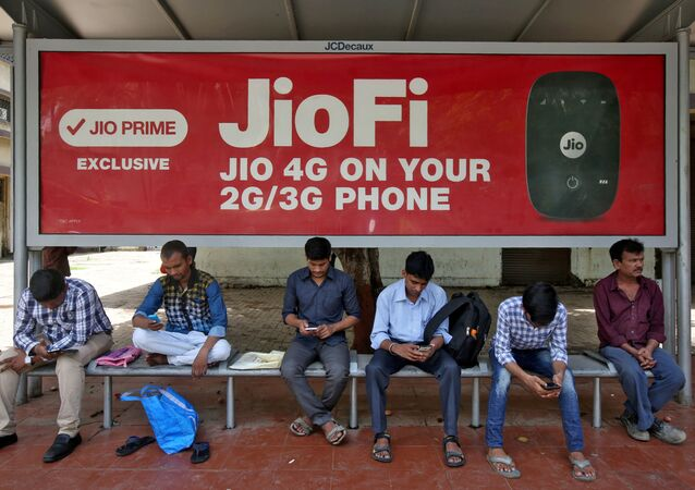 Commuters use their mobile phones as they wait at a bus stop with an advertisement of Reliance Industries' Jio telecoms unit, in Mumbai