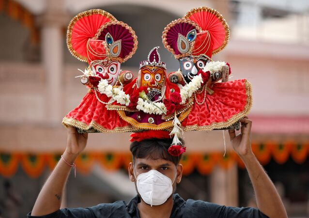 A Hindu devotee, wearing a protective face mask, carries idols of Hindu Lord Jagannath, his sister Subadhra and brother Balabhadra, as he arrives to attend the annual Rath Yatra