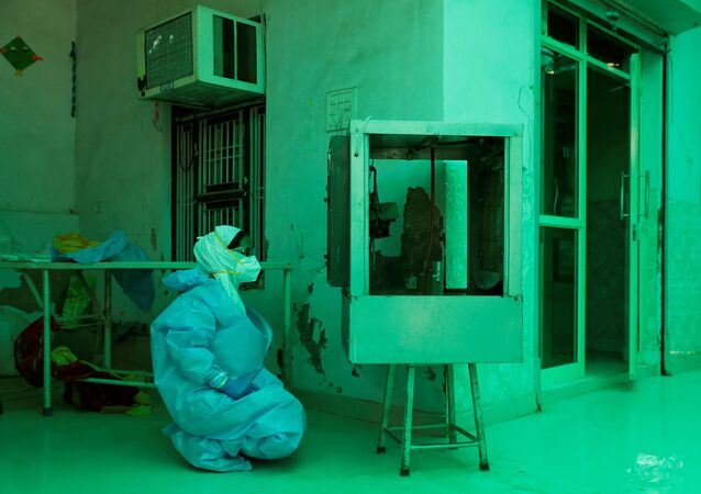 A medical worker wearing Personal Protective Equipment (PPE) relaxes in front of an air cooler