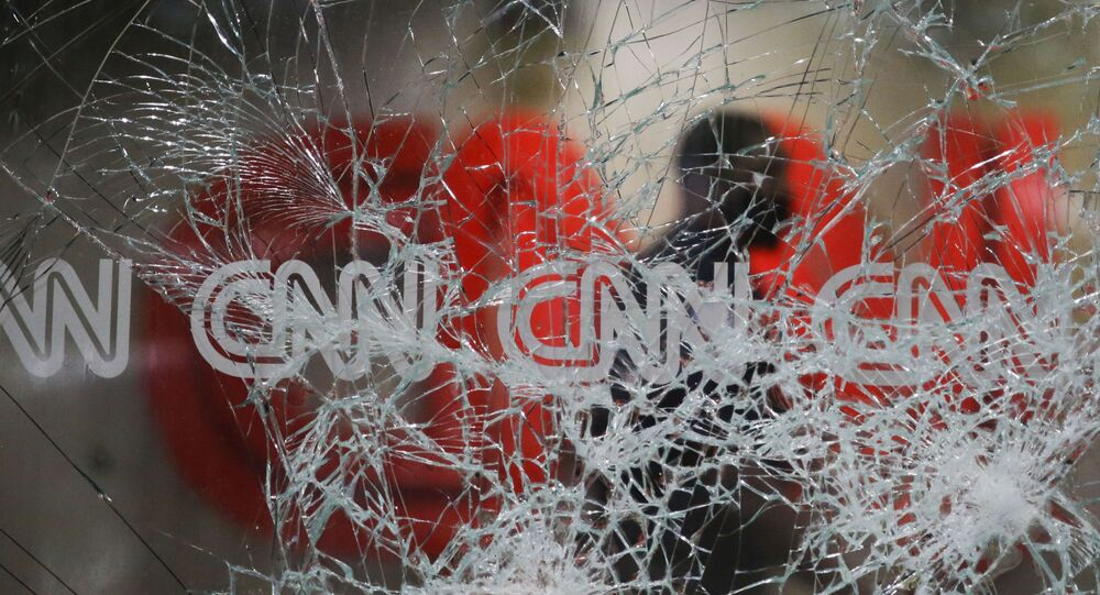 A security guard walks behind shattered glass at the CNN building at the CNN Center in the aftermath of a demonstration against police violence on Saturday, May 30, 2020, in Atlanta.