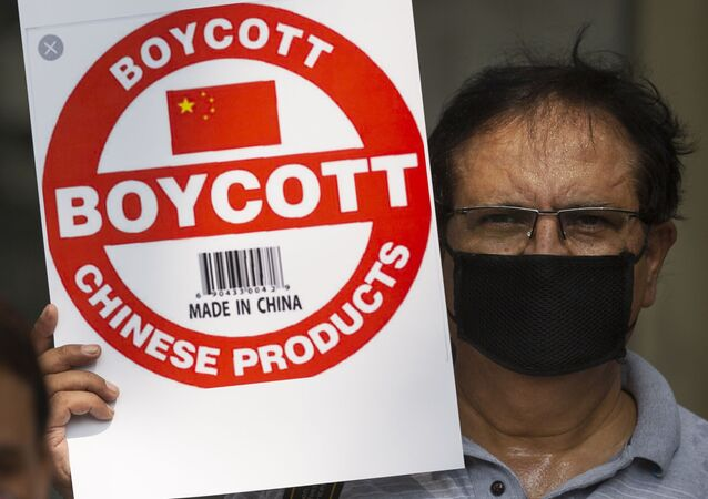 An Indian journalist holds a placard calling for boycott of Chinese products