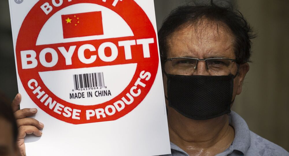 An Indian journalist holds a placard calling for a boycott of Chinese products
