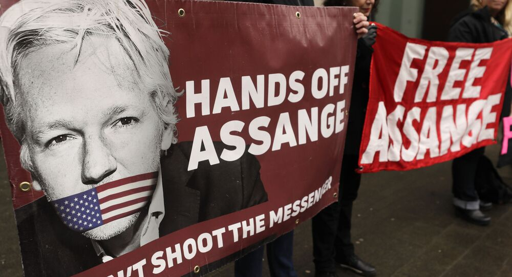 Demonstrators hold banners outside Westminster Magistrates Court in London, Wednesday, Feb. 19, 2020. A case-management hearing regarding Julian Assange will be heard at the court Wednesday