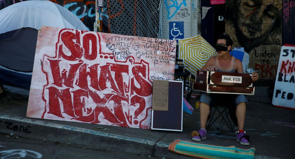 A musician performs outside the Seattle Police Department's East Precinct in the CHOP area as people continue to occupy space and protest against racial inequality in the aftermath of the death in Minneapolis police custody of George Floyd, in Seattle, Washington, U.S. June 25, 2020