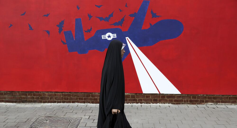 A woman walks past a new anti-U.S. mural on the wall of former U.S. embassy portraying the interception of Global Hawk US drone by Iran in Persian Gulf, after an unveiling ceremony in Tehran, Iran, Saturday, Nov. 2, 2019.