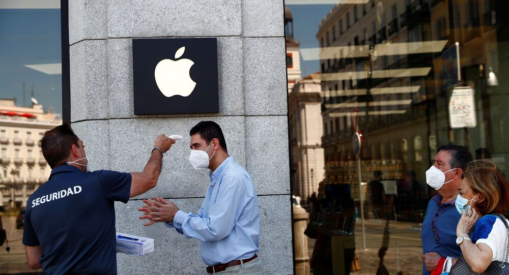 A man wearing a protective mask gets his temperature taken before entering an Apple store, amid the coronavirus disease (COVID-19) outbreak, in Madrid, Spain, June 30, 2020.